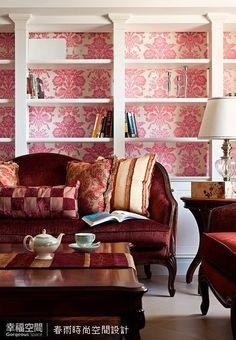 暗紅絨布沙發後的大型層架兼具展示櫃及書架功能,設計師在層架背牆貼飾紅系圖騰壁紙,豐富空間彩度,營造皇家貴族氣勢。