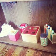 A great example of a Montessori infant shelf with triangle stackers, nesting bowls, nesting cubes, shape sorting box, wooden pop-up toy and a colorful rice shaker jar.