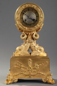 Gilt and chiseled bronze mantel clock decorated with dolphins. They support the silvered dial which is embellished with Zodiac Signs. The clock rests on a rectangular base adorned with marine trophy, above four shell shaped feet. Original movement, cleaned and in working condition. Signed GRANDVOINNET in Paris.