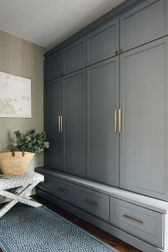 Mudroom with charcoal gray cabinets featuring brass pulls furnished with a leopard print stool on top of a blue runner.