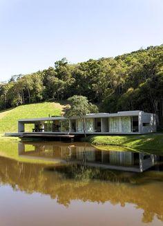 Galeria da Arquitetura | Residência São Luis do Paraitinga - Localizada em uma pequena clareira, a residência tem à frente um lago e atrás, a mata atlântica: