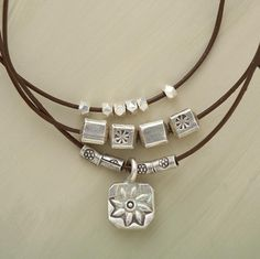 """Three graduated lengths of leather cord are strung with pure silver adornments hand made by Thai artisans. The longest strand dangles a flower-stamped charm. A Sundance exclusive with hook and eye clasp. Leather relaxes with wear. 16""""L."""