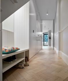 Facet House by Platform 5 Architects A corridor connects the extension with the house's main entrance. It is lined with tongue-and-groove panelling, which integrates practical spaces including a WC, a utility room and storage nook for coats and shoes.