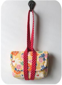 Cute bag...I like the combo. handle/closure. You'd have to sew it onto the bottom of the bag and (on the other side of the strap) to the top of the bag.
