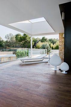 Chiralt Arquitectos I Terraza con lucernario, mobiliario minimalista y suelo de parquet.