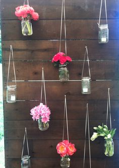 hanging mason jars with flowers and votives... Hanging one of the barn walls for detail...
