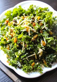 Lemon Parmesan Kale Salad: Ingredients For the dressing: 2 Tablespoons olive oil, 1 Tablespoon lemon juice, 1 Tablespoon basil, minced, ½ Tablespoon parmesan cheese, grated, ½ small clove garlic, minced, ½ Tablespoon shallots, minced, ½ Tablespoon Dijon mustard, For the salad: 1 bunch organic green kale, stemmed 1 cup romaine lettuce, chopped 2 tablespoons freshly grated parmesan cheese, ½ cup golden raisins, 2 Tablespoon currants, 1 tablespoon slivered almonds | layersofhappiness