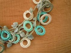 For this necklace we crocheted around little plastic rings with turquoise, aqua, sage and cream thread. They are crocheted together using sage thread and chipbeads.  Length: 45-50 cm / 18-20 in