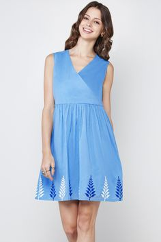 Sleeveless dress in light blue cotton mul that has an overlap V-neckline with a gathered waist and delicate print on the hem.