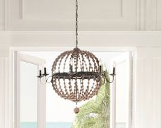 A neutral chic chandelier made of wooden beads hanging from the ceiling.