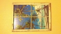 Window frame with beach poster attached behind for beach themed bedroom.