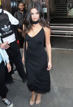 Inspiring Selena Gomez Gives a stunning look in skinny tie scarf. she opted for classy black again and put her slim physique on show in the body skimming dress.Selena wore a dress which had a demure hemline falling just above her ankles and a very low cut v-neckline.The actress and singer tied a skinny black scarf around her neck and completed her style with silver heels and a loose curled hairdo. #SelenaGomez #Celebrity #Fashion #Style #Inspiring