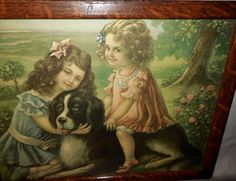 """This is a vintage print of two Victorian style girls with their Newfoundland dog. It is titled """"Rover and His Friends"""" and also has the No. 707 at the lower right. It is in an oak wood frame with an attractive grain. It has glass, a cardboard b..."""