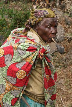 An elder pygmy lady, said to be 100, smoking a pipe in her village near Kisoro, Uganda.