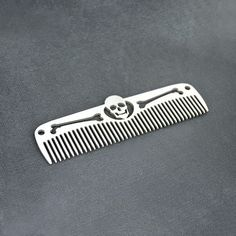 Crafted from 1/10th inch thick aerospace Grade 5 titanium alloy, the Skull & Bones Titanium Comb weighs in at under 1 oz. A skull appears to float in the spine of the comb through the creative use of negative space, while holes machined at each en...