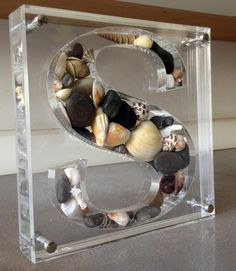 Yael man custom made letters from plexiglass filled with different elements. This S is filled with SeaShells taken from Srilanka