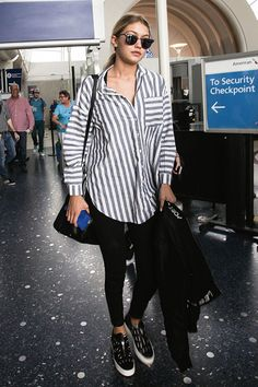 Gigi Hadid had some seriously cool airport style when she was spotted arriving at LAX on July 20 wearing an oversized boyfriend shirt. We love this cozy, yet chic look — it's ideal for travel! Want to try the trend? SHOP it here!