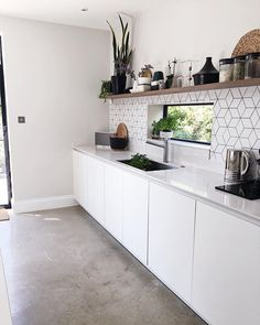 White matte kitchen with open shelves | Grey concrete floors | Narrow window behind sink by SHnordic
