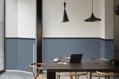 Mur bicolore bleu et blanc dégradé avec une frise horizontale noire dans la salle à manger