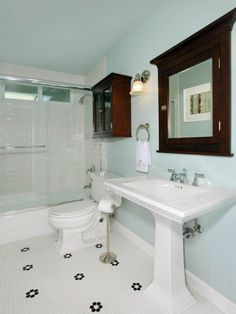 This bathroom's light blue walls and traditional touches keep this no-fuss space functional. The hexagon tile floor, pedestal sinks and dark-stained medicine cabinets create a classic design style throughout the space.