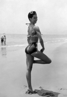Ballet dancer Cyd Charisse posing impishly while standing on one leg at Santa Monica beach, 1945.