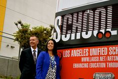 """LAUSD Superintendent Dr. John Deasy and LAUSD District 6 Board of Education Member Nury Martinez stand with the Barbara Kruger public art piece """"School Bus,"""" an LA Metro bus carrying messages about art and education throughout Los Angeles."""