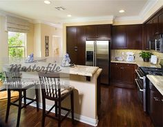 Traditional kitchen with breakfast bar and dark wood cabinets Stock Photo - Premium Royalty-Free, Code: 647-02641762