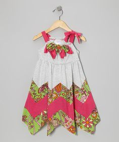 Sweet rosettes at the neck and a bold zigzag at the hem make this dress a real stunner. Little touches of paisley and a tie strap spark up the fun factor for a complete package. Soft, stretchy fabric makes for a comfy statement piece.