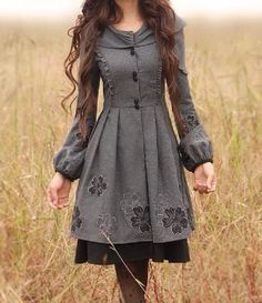 Grey Merino Wool Dress, buttons down front, with fitted sleeves and blousing at the wrist.  Hooded. Floral embroidery.  Worn over black petticoat.