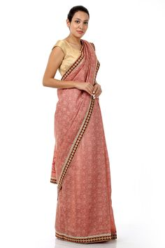A peach silk sari, it is luxuriously crafted in kosa silk blended with cotton for an elegant finish. This beautiful piece is designed with an elaborate border and exquisite floral details cascading the silhouette. It comes with a contrasting blouse piece.