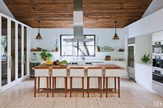 In the Los Angeles home of fashion designer Jenni Kayne and her husband, real-estate agent Richard Ehrlich, a ceiling of reclaimed timber brings warmth to the modern kitchen. Architecture firm Standard helped make it one of the most used rooms in the house, with the compelling mix of French industrial pendant lights from the 1920s and white-lacquer cabinetry.