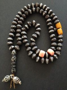 A Silver inlaid black coral bead Yusr, which has two pieces of coral and two pieces of amber in it.  © Jose M Pery