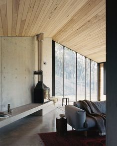 """At the far end of the """"living shed"""" is a fireplace and concrete bench, which offers a contemplative space for reading and watching the bushland through the windows. #dwell #australianhomes #farmhomes #vacationhomes #moderndesign Victoria Australia, Australian Sheds, Australian Houses, Agricultural Buildings, Concrete Bench, Journal Du Design, Pivot Doors, Joy Of Living, Aphasia"""