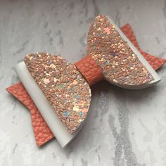 Size: Larger Bow - 3Inches long from end to end. Description: This gorgeous Hair Bow is a combination of an Orange Leatherette and finished with a stunning White Mirrored Fabric and Peach Glitter. These Hair Bow will be attached to a crocodile clip. Prices are per hair bow. This hair