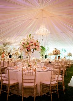 wedding tent with tall, grandiose flowers for the centerpieces