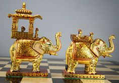 Ambawari Gold Painted Buffalo bone chess set from Rajasthan, India. The pieces represent two armies of Rajasthan and are painted to show uniforms and turbans, in red and green colours. The pawns are carved as foot soldiers, bearing arms. The Rooks are fighters seated on camels, the Knights are riders mounted on horseback and the Bishops are warriors carried by elephants. $1,650