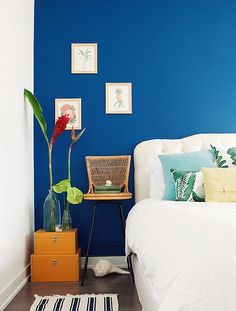Beautiful cobalt blue accent wall with tropical accessories and artwork.