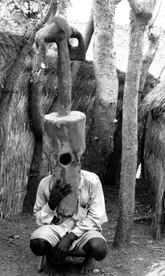 A man from Kufuru village demonstrates how a vertical mask is worn and stabilized. Photograph by Arnold Rubin, April 20, 1970, Kufuru village (Yendang peoples), Rubin Archive, Fowler Museum at UCLA.
