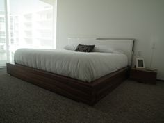 Cama King size con base de madera de nogal y respaldo en acero y tela blanca