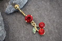 This golden cherry dangle belly button ring features a high luster red crystal c. - This golden cherry dangle belly button ring features a high luster red crystal cut gem with a capti - Belly Button Piercing Rings, Gold Belly Button Rings, Cute Belly Rings, Belly Button Jewelry, Nose Rings, Piercing Cartilage, Bellybutton Piercings, Tongue Piercings, Cartilage Piercings