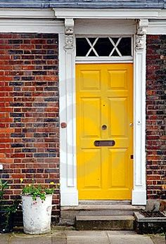 brown brick house with yellow front door | Yellow represents mental clarity, wisdom, confidence, happiness ...