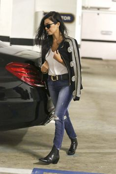 Kourtney Kardashian wears a t-shirt, embroidered jacket, western belt, distressed jeans, and black ankle boots