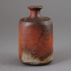 Isezaki Mitsuru  |  Bizen squared, stoneware sake bottle (1983), dry brown body with grey and ochre flashes, mottled green glaze to the shoulder, incised makers mark (H 11.5cm, D 7cm).