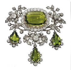 A SET OF ANTIQUE PERIDOT AND DIAMOND JEWELLERY   Comprising a devant de corsage, designed as a cushion-shaped peridot in an old-cut diamond frame, to the diamond flowering surround, suspending three pear-shaped peridot and diamond pendants, a pair of earrings en suite, with detachable pendants, mounted in silver and gold, circa 1825, Austrian, brooch 9.3 cm, earrings 7.1 cm  Probably by Kochert