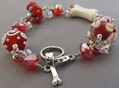 Dog Bone Bracelet with red and white artisan lampwork beads, sparkling red chunky crystals, white porcelain dog bone, and silver dog collar and bone toggle clasp.  Handmade by For Love of a Dog Jewelry & Gifts