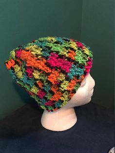 Crocheted rainbow colored bun hat