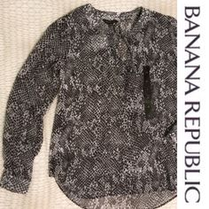 NWT Banana Republic blouse Black and white patterned blouse from Banana Republic.  Long sleeves with small buttons at the bottom of the sleeves and extra buttons provided.  Ties at neck.  Slight high-low fit.  New with tags and never worn Banana Republic Tops Blouses