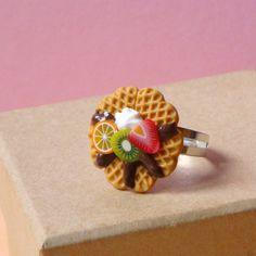 Cette délicieuse bague en forme de gaufre chocolat-fruits est modelée en pâte Fimo. Les gaufres sont en forme de cœur, recouvertes d'un coulis de choc