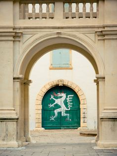 Green doors with a painted Styrian Panther: Graz, Austria / photo by LaPanteraRosa.