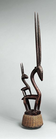 Headdress: Female Antelope (Ci Wara)  Date: 19th–20th century Geography: Mali, Ségou region Culture: Mali; Bamana peoples Medium: Wood, fibers Dimensions: H. without basket 38 1/2 in. (97.8 cm) H. with basket 42 1/2 in. (108 cm)